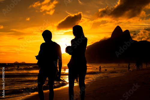 Silhouette of a Couple Walking in Ipanema Beach in Rio de Janeiro by Sunset with Mountains in Background