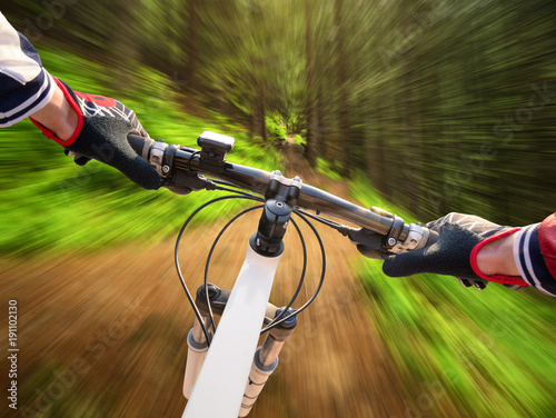 Fast ride on bike in summer forest. Sport and active life concept