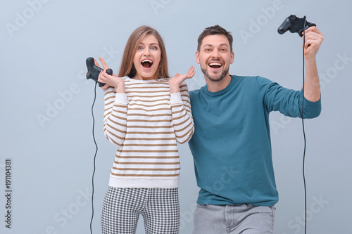 Emotional couple with video game controllers on color background