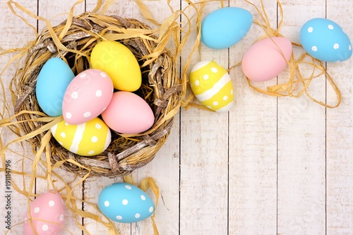 Springtime nest with pink, yellow and blue painted Easter Eggs. Corner border against a rustic white wood background.