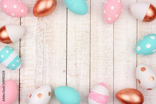 Easter egg frame. Rose gold, pink, turquoise and white colors on a white wood background.