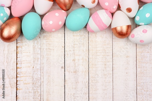 Easter egg top border. Rose gold, pink, turquoise and white colors on a white wood background.