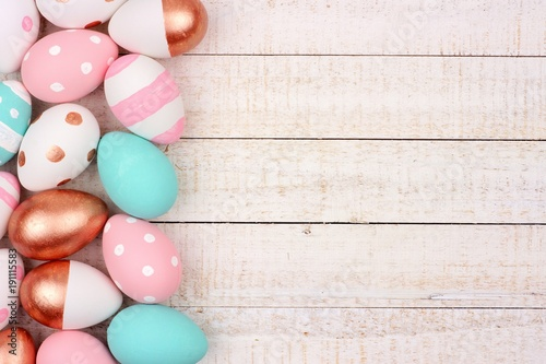Easter egg side border. Rose gold, pink, turquoise and white colors on a white wood background.