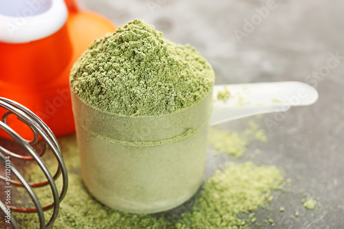 Hemp protein powder in measuring scoop on table