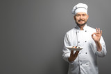 Handsome male chef holding plate with dish on gray background - 191121171