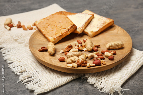 Wooden plate with toasted bread and nuts on table