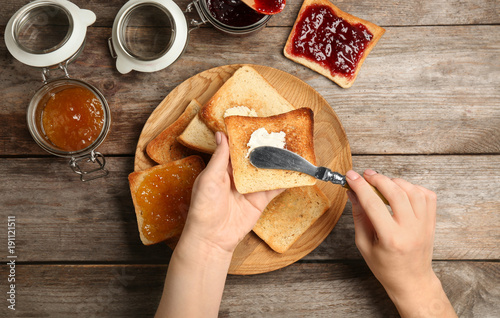 Woman spreading butter on toasted bread over table, top view