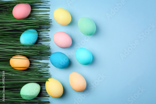 Dyed Easter eggs and decorative grass on color background