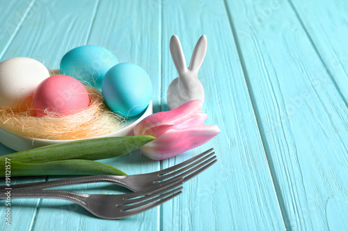Beautiful festive Easter table setting with painted eggs and tulip on wooden background