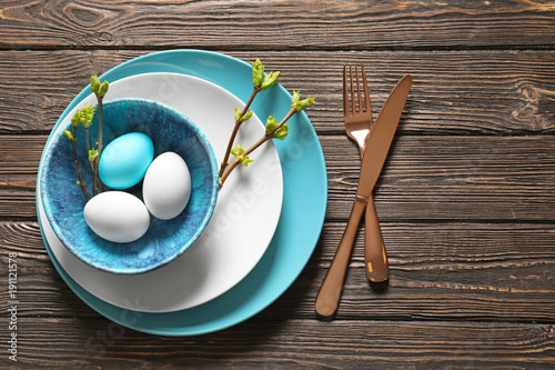 Beautiful festive Easter table setting with eggs on wooden background