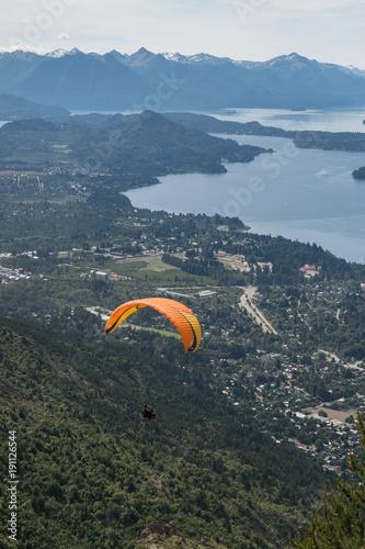 Retrato de parapente color naranja volando sobre ciudad con lago azul y montañas de fondo
