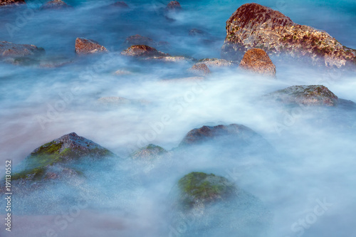 Tuinposter Blauwe hemel Sea rocks in haze at sunset