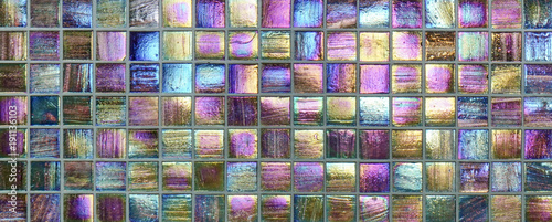 Colorful square metallic tiles on a wall or floor. Blue, green, teal, yellow, orange, purple reflective tile pattern. Shiny tile pattern with purple, teal, green, blue, yellow, gold and orange.