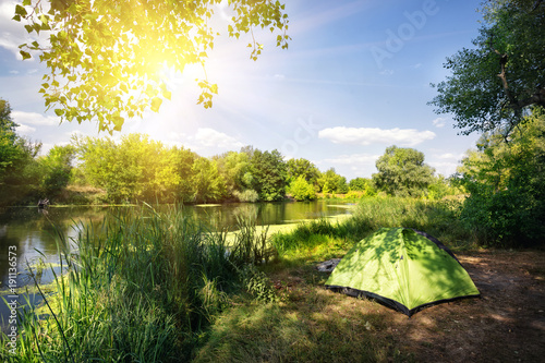 Fotobehang Landschappen Green tent on the river bank in the bright sun
