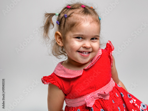 Portrait of a beautiful little cheerful girl on a white background. The child laughs