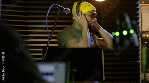 Male black singer in a sound booth