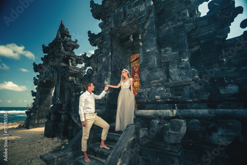 Portrait of happy couple near traditional gate. Traveling at Bali