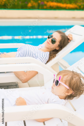 Endless summer. Cute baby and mother relaxing at sunbed