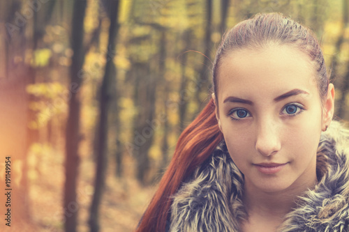 Cute beautiful pretty redhead female teenager in autumn forest. Close up charming portrait, shallow depth of field, toned.