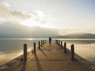 Traveler standing on Pier Lake mountain Landscape morning scene Wanderlust