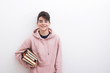 teenage student with books on the white wall