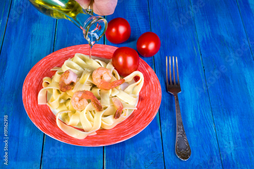 Spaghetti and shrimp in a white dish with a red border, and red tomatoes beside, to. A humans hand pours a dish from a transparent jug with oil. The concept of cooking vegetarian food.