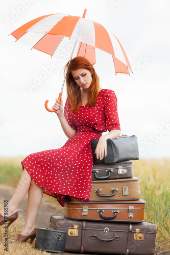 girl with umbrella and bags at countryside