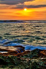 Ein traumhafter Sonnenuntergang mit warmen leuchtenden Farben in gold, orange, rot, über dem wilden Indischen Ozean in Asien auf der bezaubernden tropischen Insel Sri Lanka