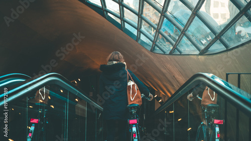 Woman on an escalator with bike