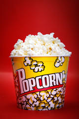Full yellow bucket of popcorn on red background