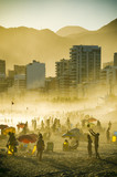 Dramatic scenic sunset view of golden mist billowing over Ipanema Beach with the city skyline silhouette and mountains of Rio de Janeiro, Brazil