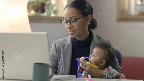 Mother holding baby and working at computer