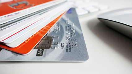 Close up of credit cards stack near white computer keyboard, online payments or transfer concept