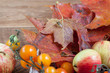 Fruits and autumn leaves are lying on a wooden desk. Autumn still life.