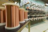 Standard copper wire enamel in a bobbin on the table, steel floor in the factory. The backdrop is a machine. Winding machine - 191196964