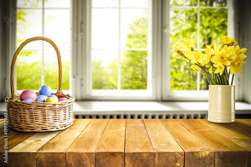 Foto Murales Easter eggs on wooden table in basket and background of window of spring.
