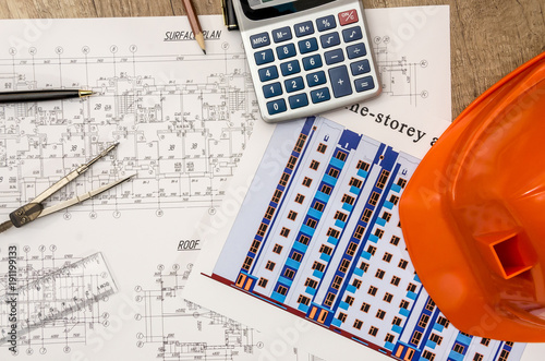 hard hat with blueprints and rulers, pen, calculator on desk