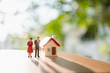 Quadro Miniature people, man and woman standing with mini house on green nature background using as relationship and family concept