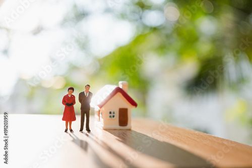 Miniature people, man and woman standing with mini house on green nature background using as relationship and family concept