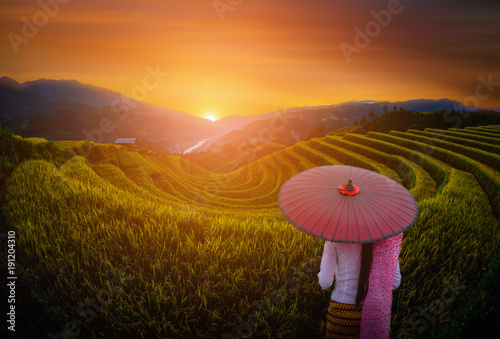 In de dag Rijstvelden Woman holding traditional red umbrella on rice fields terraced with wooden pavilion at sunset in Mu Cang Chai, YenBai, Vietnam.