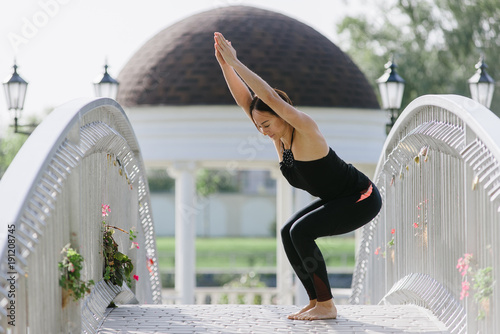 Fotobehang School de yoga A woman yogi makes asanas on the bridge in the summer in a park.