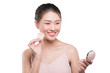 Portrait of beautiful young asian woman with perfect fresh clean skin applying cosmetic brush and use mirror.