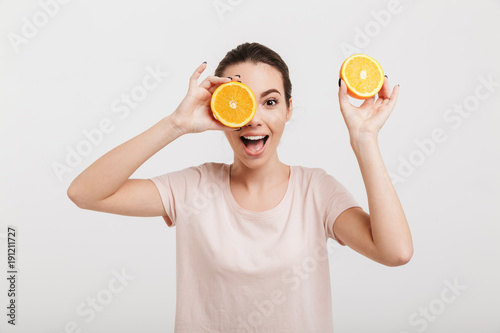 emotional young woman covering one eye with half of orange isolated on white