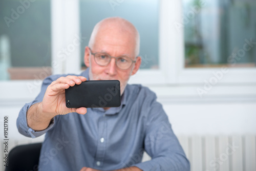 mature handsome man using smartphone at home