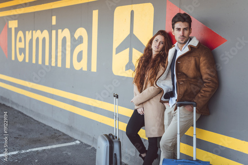 Young couple with suitcases at terminal