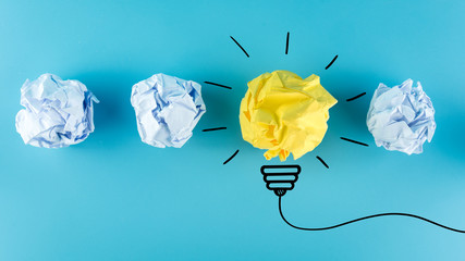 Inspiration concept crumpled paper light bulb metaphor for good idea, New Idea Concept. Crumpled Paper Balls on blue background. © Worawut