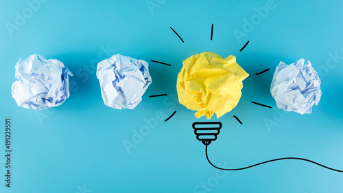 Inspiration concept crumpled paper light bulb metaphor for good idea, New Idea Concept. Crumpled Paper Balls on blue background.