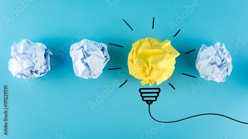 Inspiration concept crumpled paper light bulb metaphor for good idea, New Idea Concept. Crumpled Paper Balls on blue background.