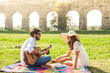 Beautiful girl with hat with young man playing guitar in park on a sunny day. Happy couple sitting on colorful picnic blanket in front of roman aqueduct ruins in rome.