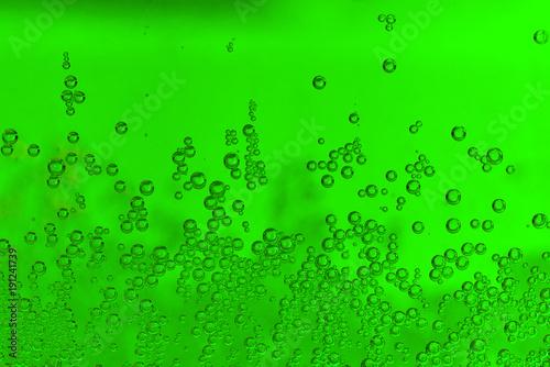 Leinwandbild Motiv The green bubbles in soda water as a texture.